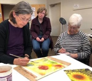 Mary Anderson showing watercolor techniques to students